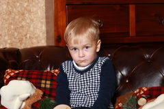 A little boy in a sweater sitting on a brown sofa Royalty Free Stock Images