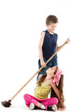 Little boy sweeping angry little girl Stock Photos