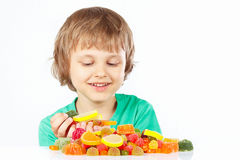 Little boy with sweets and jelly candies on white background Stock Images