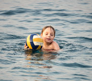 Little boy swimming with ball Stock Image