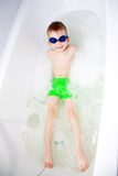 Little boy swimming in bath in glasses for diving Royalty Free Stock Photography