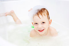 Little boy swimming in bath and smiling Royalty Free Stock Images