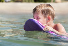 Little boy swimming on board near the beach Stock Photography