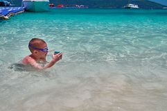 Little boy in swimming glasses plays in turquoise water with action camera in protective box. Child swims in waters tropical sea. Royalty Free Stock Photo