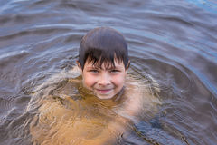 Little boy swimming in a lake Stock Images