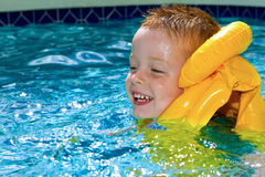 Little boy swimming with life vest on.  stock photography