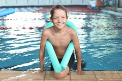 Little boy with swimming noodle. In indoor pool royalty free stock photos