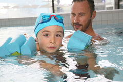 Little boy in swimming pool with armbands Stock Images
