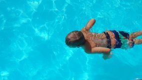 Little boy swimming in pool and dives underwater. View from above stock video