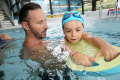 Little boy in swimming pool with his trainer Royalty Free Stock Photo