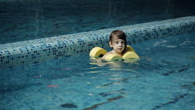 Little boy swimming in the pool at the leisure center stock footage