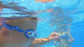 Little Boy Swimming in the Pool between Relatives. Slow motion shot of little boy in goggles swimming underwater in swimming pool between his relatives stock footage