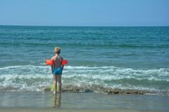 Little boy with swimming sleeves, stands on the beach Royalty Free Stock Image