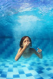 Little boy swimming underwater in the blue pool royalty free stock photography