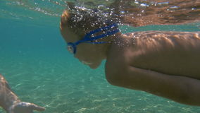 Little Boy Swimming Underwater in the Sea. Slow motion shot of little boy in goggles swimming underwater in the sea towards his mother holding stones in his stock video footage