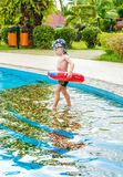 Little boy swims, cheerful child jumping in the pool in the circle, open-air swimming pool, Royalty Free Stock Images