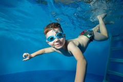 Little boy swims underwater in the pool, smiling, blowing bubbles and looking at me. The view from under the water. Close-up. Horizontal orientation Royalty Free Stock Photos
