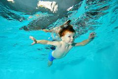 The little boy swims underwater and soars like a bird, spreading his hands on a blue background. Portrait. Shooting under water at the bottom. Horizontal view Stock Images
