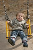 Little boy on a swing. Small blonde boy playing on the swing. 2 years old boy is smiling and looking at camera Stock Photo