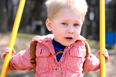 Little Boy Swinging. Young boy having fun on a swing, looking at the camera Stock Images