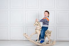 Little boy swinging on wooden horse. funny three-year-old boy in jeans and sweater on white background. Carefree childhood. Baby smile Royalty Free Stock Images