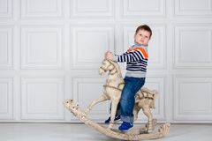 Little boy swinging on wooden horse. serious three-year-old boy in jeans and sweater on white background. Carefree childhood Royalty Free Stock Image
