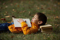 Little boy sying on stack of books Stock Photo
