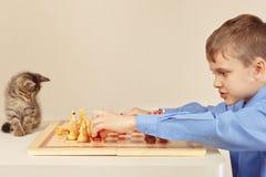 Little boy with tabby kitten plays chess. Little boy with a tabby kitten plays chess Stock Photography