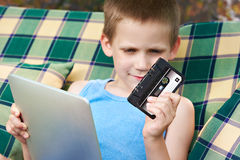 Little boy with tablet and audio cassette Royalty Free Stock Image