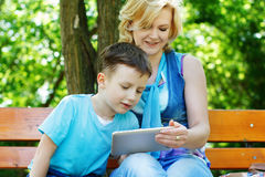 Little boy with tablet and mother Royalty Free Stock Image