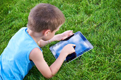 Little boy with tablet pc on grass Stock Image