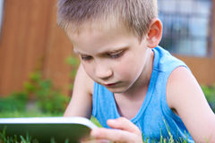 Little boy with tablet pc on grass Stock Photography