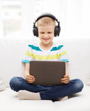 Little boy with tablet pc and headphones at home Stock Photography