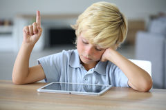 Little boy with tablet raising hand at school Royalty Free Stock Photo