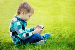 Little boy with tablet sit on the grass Royalty Free Stock Photography