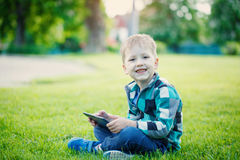 Little boy with tablet sit on the grass Royalty Free Stock Image