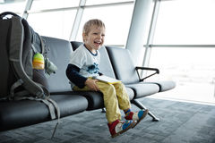 Little boy with a tablet sitting in an airport departure hall Royalty Free Stock Photography