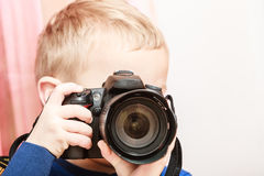 Little boy take photo with camera. Technology and childhood. Discovering and fun. Child play and take photo in home. Boy wear blue shirt and hold camera Stock Image