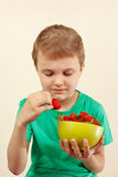 Little boy takes fresh ripe strawberry from the bowl Stock Image