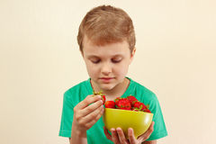 Little boy takes fresh strawberry from the bowl Stock Image