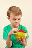 Little boy takes fresh sweet strawberry from the bowl Royalty Free Stock Images