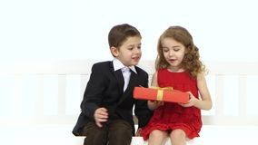 Little boy takes a pair of pants and gives the girl in return she kisses him on the cheek. White background stock footage