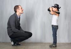 Little boy takes a photo of a man Stock Photo