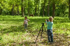 A little boy takes pictures a gir Stock Images