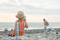Little boy takes pictures on the smart phone. Sits on a pebble b stock photos