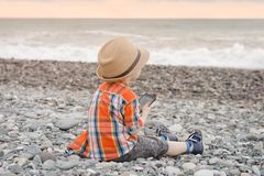 Little boy takes pictures on the smart phone. Sits on a pebble b royalty free stock photo