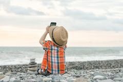Little boy takes pictures on the smart phone. Sits on a pebble b stock photo