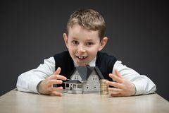 Little boy taking away house model and pile of coins Stock Photos