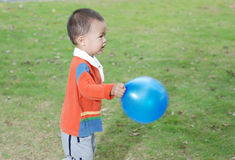 Little boy taking a balloon Stock Images