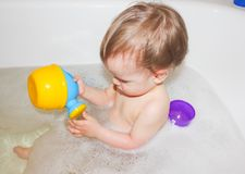 little boy taking a bath with foam and playing with a toy watering can. The child sits in the bubble bath.. royalty free stock images